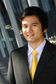 Asian business man dressed in suit and tie, smiling. — Stock Photo