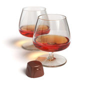 Cognac glasses and chocolate candy — Stock Photo