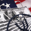 100 Dollar Bills And Stethoscope Over American Flag - Stock Photo