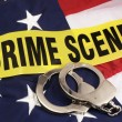 Crime Scene Tape And Hand Cuffs Over AmericFlag — Stock Photo #12072171