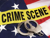 Crime Scene Tape And Hand Cuffs Over American Flag — Stock Photo
