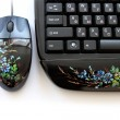 Royalty-Free Stock Photo: The computer keyboard and mouse with an art list.