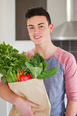 Good looking young man holding bag of fresh groceries — Stock Photo