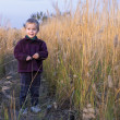 A little boy stands amid the tall grass. — Stock Photo