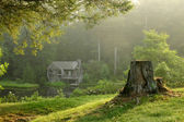 Old watermill in forest at dawn — Stock Photo