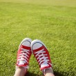 Stock Photo: Feet in sneakers in green grass