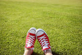 Feet in sneakers in green grass — Stok fotoğraf
