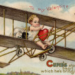 A vintage Valentine card with cupid flying an airplane with a stolen heart - Stock Photo