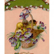 A vintage Easter postcard of a basket full of chicks and violets hanging from a pussy willow branch - Stock Photo