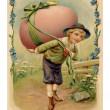 Stockfoto: Vintage Easter postcard of boy with large Easter egg on his back