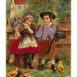 A vintage Easter postcard of a little boy and girl surrounded by chicks - Stockfoto