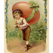 Stockfoto: Vintage Easter postcard of child with large egg on his back