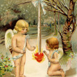 A vintage Valentine card with two cherubs warming up next to a heart on fire — Stock Photo