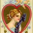 A vintage Valentine card with cupid flying over a woman with a feather fan — Stock Photo