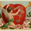 Stock Photo: A vintage Valentines card with a cherub patching up a broken heart