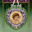 Stock Photo: Vintage Valentines postcard with cherub holding love letter in garland of violets