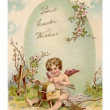 图库照片: A vintage Easter postcard of a cupid making arrows and a large Easter egg