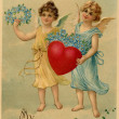 A vintage Valentine postcard with two angels holding a heart and forget-me-not flowers — Stock Photo
