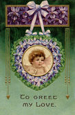 A vintage Valentines postcard with a cherub holding a love letter in a garland of violets — Stock Photo