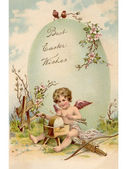 A vintage Easter postcard of a cupid making arrows and a large Easter egg — Stock Photo