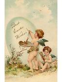 Een vintage pasen ansichtkaart van twee engeltjes schilderen een easter egg — Stockfoto