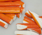 Fresh crab sticks cut on white kitchen table — Stock Photo