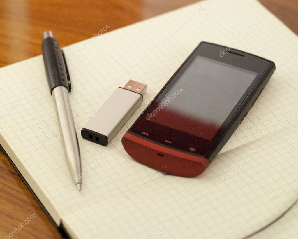 Open book,memory usb pendrive, phone and pen on the table — Stock Photo #11921553