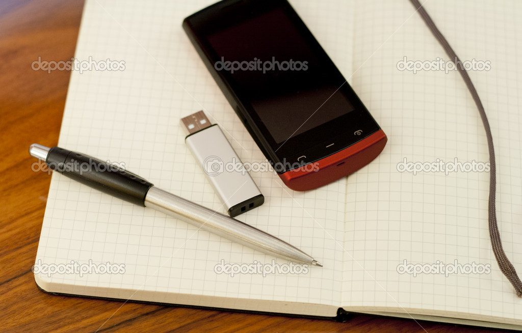 Open book,memory usb pendrive, phone and pen on the table — Stock Photo #11921570