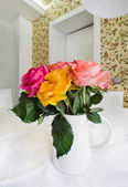 Colored roses in white vase — Stock Photo