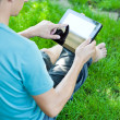 A young man uses tablet computer outdoor — Stock Photo