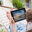 Stock Photo: Musing tablet computer while relaxing in hammock