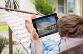 Man using a tablet computer while relaxing in a hammock — Stock Photo