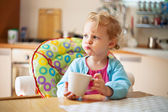 Portrait of little girl having drink in the kitchen — Stock Photo
