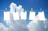 Blank photos hanging on a clothesline, blue sky on background — Stock Photo