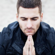 Praying man in dark clothing on a light background — Stock Photo