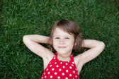 Portrait of a smiling little girl lying on green grass — Stock Photo