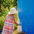 Adorable small girl painting on a fence - Stock Photo