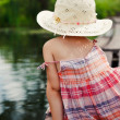 Adorable small girl sitting on the wooden bridge and thoughtfully looking on the river — Stock Photo