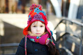Small adorable girl in hat and knitted scarf looking very dissatisfied — Stock Photo