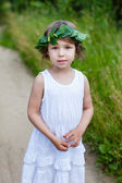 Portrait of cute girl with a wreath outdoor — Stock Photo