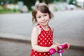 Portrait of cute toddler girl in red dress on the scooter — Stock Photo