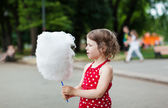 Beautiful little girl eating cotton candy in the park — Stock Photo