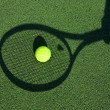 Shadow of a tennis racket in hand with a ball — Stock Photo #12268608