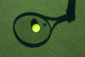 Shadow of a tennis racket in hand with a ball — Stock Photo