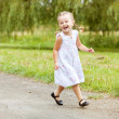 Happy little girl running on road — Stock Photo
