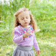 Beautiful child blows on dandelion in the summer — Stock Photo