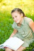 Closeup portrait of teen girl on a grass with book — Stock Photo