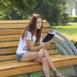 Young woman sitting on a bench reading a book in a park — Stock Photo