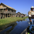 Burmese boatman driving through floating village, Inle lake, Shan state, Myanmar, Southeast Asia — Stock Photo