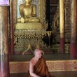 Monk sitting near statue of Buddha, Jumping cat Monastery, Inle lake, Shstate, Myanmar, Southeast Asia — стоковое фото #11809110